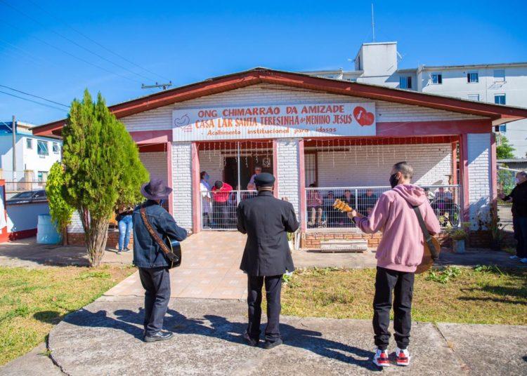 Iniciativa contou com a participação de artistas voluntários, que se apresentaram nos portões de cinco lares conveniados com a Prefeitura de Canoas, levando música para comemorar o Dia das Mães — Foto: Pablo Reis
