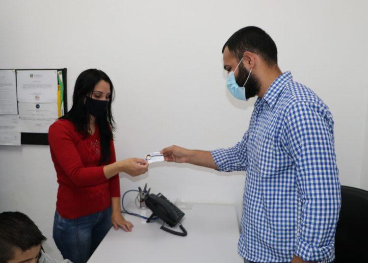 Denise Franciele Nunes e o filho recebendo a Ciptea do asssessor de Políticas Públicas para a Pessoa com Deficiência, Bruno Peixoto — Divulgação/PMG